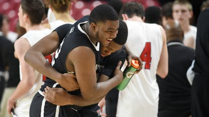 Dreshawn Hodges, left, embraces Lake Clifton teammate Zevon Hughes following their win over Southern-Garrett during the MPSSAA Class 1A boys basketball state championship at University of Maryland on Saturday.