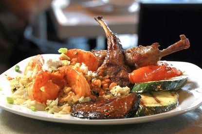 The surf and turf with shrimp saganaki and lamb chops at Ethos Greek Bistro, located in the Promenade Coconut Creek.
