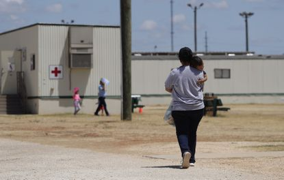 In this Aug. 23, 2019 file photo, immigrants seeking asylum walk at the ICE South Texas Family Residential Center, in Dilley, Texas. A federal judge on Wednesday, Nov. 18, ordered the Trump administration to stop expelling immigrant children who cross the southern border alone, halting a policy that has resulted in thousands of rapid deportations of minors during the coronavirus pandemic.