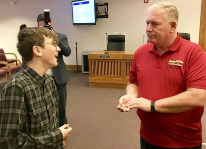 Connor Sheffield, left, smiles as he receives a challenge coin Wednesday from Havre de Grace City Councilman David Martin. The Havre de Grace mayor and City Council approved a resolution Wednesday expressing the city's support for Connor as he prepares to testify in Annapolis next week on bills allowing youths prescribed medical cannabis to take their medication on school grounds.