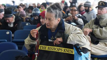 Mary Abb Stefko, Indian Head, prays the Rosary at a Silence Stops Now rally at the MECU Pavilion in November. The rally called for the end to clerical silence around sexual abuse. Kim Hairston/Baltimore Sun staff.