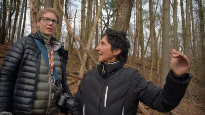 Elaine Reinhold left, and Catherine Campinos walk through a wooded area near Lake Linganore where Eaglehead, a new development, is in the early stages of construction.