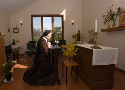 The Rev. Sister Barbara Smith, of the Order of Discalced Carmelites, prays on a prayer bench that belonged to The Rev. Mychal Judge, the Fire Department of New York's chaplain who died in the 2001 attacks on the World Trade Center, at the Episcopal Carmel of Saint Teresa in Rising Sun on Sunday, April 4, 2021. The Episcopal Carmel of Saint Teresa donated the prayer bench to the National Sept. 11 Memorial and Museum, representatives of which acquired the bench later in the morning.