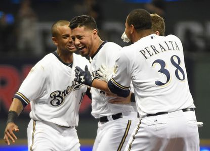 Milwaukee Brewers pitcher Yovani Gallardo (49) is surrounded by teammates after hitting a pinch hit double in the 10th inning to drive in the winning run as the Brewers beat the Baltimore Orioles 7-6 at Miller Park.