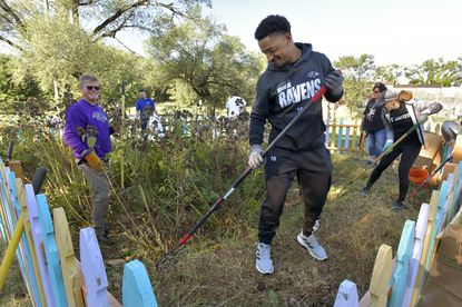 """Ravens wide receiver Tylan Wallace joins Doc Walther, a Wells Fargo employee, left, and other United Way volunteers in cleaning up a weed-filled rain garden at Benjamin Franklin High School in Curtis Bay. This is one of several events held outdoors during """"Caw to Action,"""" a United Way of Central Maryland Volunteer Day of Service in partnership with the Baltimore Ravens. Ravens fans from around the country were encouraged to participate in virtual or in-person events to give back to the Greater Baltimore Community."""