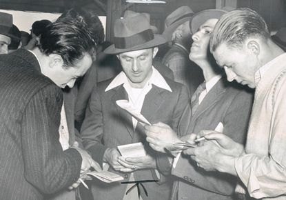 Horseplayers look over their selections under the granstand at the Havre de Grace Race Track in May 1950, the track's final meeting.