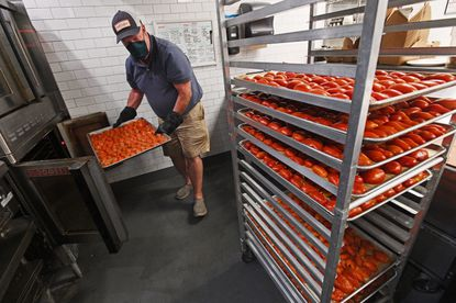 John Wagner, of Norwalk, Ct. father of one of the co-owners of Well Crafted Kitchen, takes roasted tomatoes out of the oven to process into pizza sauce.