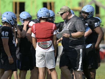 Head coach Chris Bassler talks with players during a football practice at Westminster High School Friday, August 13, 2021.