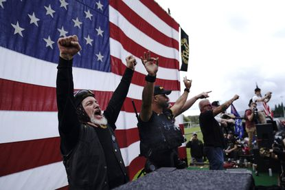 "FILE - In this Sept. 26, 2020 file photo, members of the Proud Boys, including leader Enrique Tarrio, second from left, gesture and cheer on stage as they and other right-wing demonstrators rally in Portland, Ore. President Donald Trump told the far-right extremist group to ""stand back and stand by"" during the first presidential debate in September."