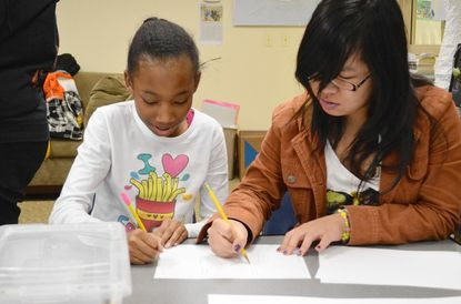 """Jemicy fifth-grader Libby Griffin, 11, and mentor Jennifer Phan, a student at Maryland Institute College of Art, work at The Jemicy School, in Owings MIlls, on March 2 on drawings for a stop-motion animated film by Libby that will help students remember that 8 x 8=64. Libby's film was part of a project called """"Memory Tricks"""" that paired eight Jemicy fifth-grade girls with eight mentors from MICA who have studied animation."""