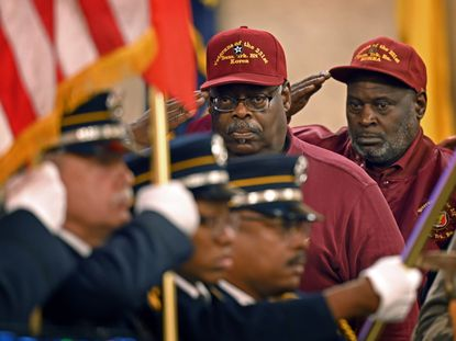 Veterans of the 231st Transportation Truck Battalion salute as an honor guard presents the colors at the opening of a Veterans Day ceremony at the War Memorial.