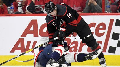 Justin Williams of the Hurricanes knocks down Dmitry Orlov of the Capitals in the second period of Game 6 of the Eastern Conference first round during the Stanley Cup playoffs at PNC Arena on April 22, 2019 in Raleigh, N.C.