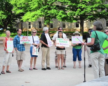 Activists hold colorful signs outside the Historic Courthouse in Towson Monday night as part of a rally coordinated by the Green Towson Alliance. Those at the rally called for more green space in Towson as downtown is rezoned and redeveloped.