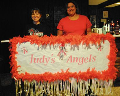Kelly Cianci, left, and Tammy Kuznik hold up a sign they made for their Relay for Life team, Judy's Angels, at Cianci's home in Finksburg July 30._- Original Credit: Natalie Eastwood/Staff photo