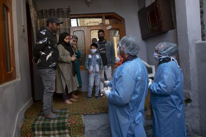 Kashmiri health workers talk to local residents during a contact-tracing drive after the first person in the region was tested positive for COVID-19 in Srinagar, Indian controlled Kashmir one month ago. For most people, the new coronavirus causes only mild or moderate symptoms. For some it can cause more severe illness. (AP Photo/ Dar Yasin)