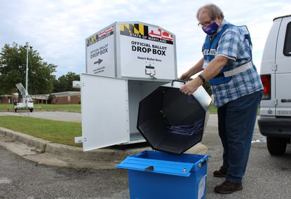 Election judges Dan Earhart retrieve ballots from the Brock Bridge Elementary School drop box on Thursday morning. The drop boxes are monitored 24/7 by security cameras, and ballots are retrieved twice daily by a team of bipartisan judges.
