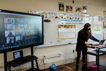 Teacher Zia Hellman works with virtual students during the first week of in-person classes at Walter P. Carter Elementary/Middle School in Baltimore, Nov. 20, 2020. Like other school districts across the country, Baltimore City Public Schools are slowly trying to get students back in the classroom. It has not been easy, but neither has remote learning.