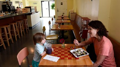 Cora Willson, left, and her grandmother Beth Burkett have lunch at Play Cafe in Hampden in 2015. The cafe, which caters to families with young children, is closing this month.
