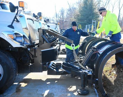 Harford County employees Ken Little, left, and Tom McGinnis work to attach a snow plow to one of the many county dumptrucks as they and other drivers prepare Thursday morning for the anticipated blizzard.
