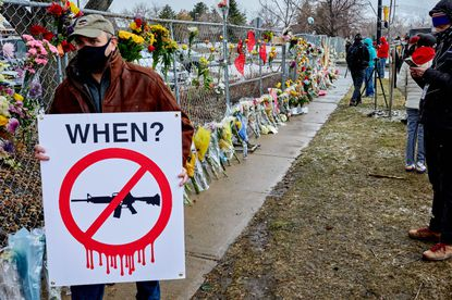 A man carries an anti-gun sign at a makeshift memorial near King Soopers grocery store in Boulder, Colo., on Tuesday, March 23, 2021, following Monday's shooting at the store which left 10 people dead. Cities across the country have tried to adopt their own regulations. Boulder's ordinance was blocked in court shortly before the mass shooting.