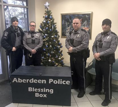 From left, Aberdeen Police Cpl. Travis Hart, Ofc. Jeanette Giganti, Sgt. Rick Clark and Ofc. Corey Lightner pose with the department's new 'Blessing Box,' which is available in the police station lobby as of Thursday. People in need can take items out of the box such as food, drinks or toiletries, plus members of the community can donate items for the box.