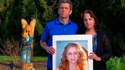 Christine and Dave McComas pose with a portrait of their daughter Grace McComas in 2013. The Woodbine girl committed suicide in 2012, leading to legislation that bears her name.
