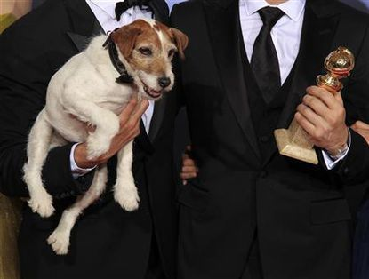 Uggie, the dog featured in ''The Artist,'' is held next to the Golden Globe award the film won.