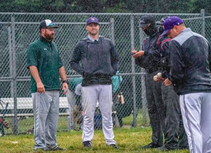 Coaches and umpires huddle together in a steady rain after the game between Atholton and Long Reach baseball was suspended in the bottom of the fourth inning on Monday, May 24.