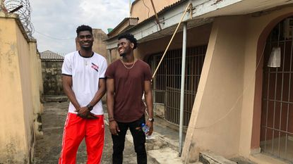 Chidi Solomon Uyaelunmo (right), a freshman forward on the Towson men's basketball team, and older brother Chinedu Victor Uyaelunmo (left), a sophomore forward for Southern California, visit the home where they grew up on the outskirts of Lagos, Nigeria.
