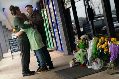 People hug outside Youngs Asian Massage where four people were shot and killed on March 17, 2021 in Acworth, Georgia. Suspect Robert Aaron Long, 21, was arrested after a series of shootings Tuesday night at three Atlanta-area spas left eight people dead, including six Asian women. (Photo by Elijah Nouvelage/Getty Images)