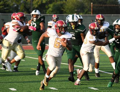 Teon Dukes carries the ball for New Town in the team's season-opening game against Milford Mill. The Titans will play in this season's first Raves RISE game when they face Owings Mills on Friday.