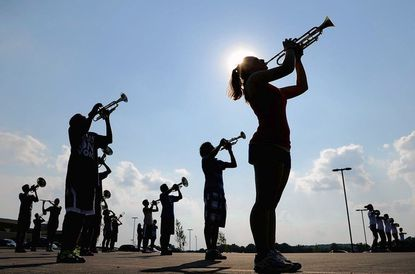 Junior trumpet player Alexis Kalivretenos, right, and other members of the Centennial marching band practice in the school parking.
