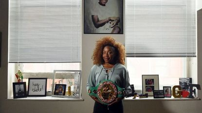 Franchón Crews-Dezurn, World Boxing Council super middleweight champion, holds her belt under a portrait of her mother, Sarah Marie Crews, who died in December 2016.