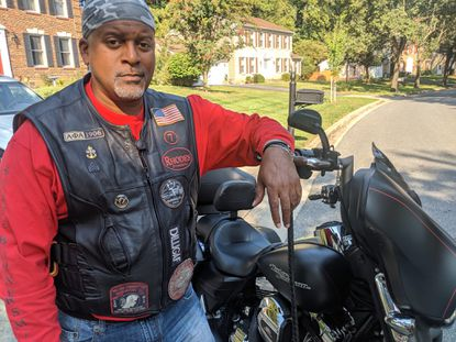 """State Burner's Motorcycle Club Bowie chapter President Rodney """"Rhodes"""" Yancey poses with his motorcycle, nickname """"Ghost,"""" at his house in Bowie Sept. 11."""