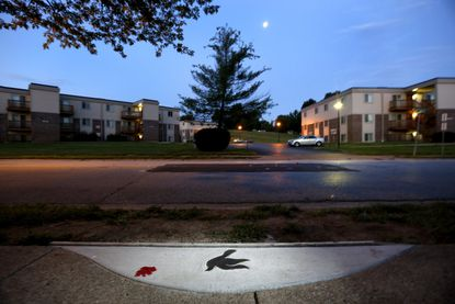 A marker in the shape of a dove is embedded in the sidewalk near the spot where Michael Brown was shot and killed by police officer Darren Wilson in Ferguson, Mo.