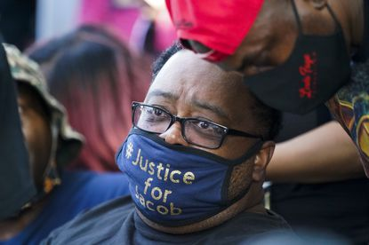 Jacob Blake's father, Jacob Blake Sr., who was shot seven times by police in Kenosha, Wisconsin, wears a Justice for Jacob mask at a rally Saturday.