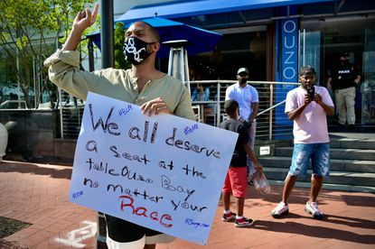 Jeremey Williams protests outside of Ouzo Bay a day after a viral video that showed a Black family being refused service by management.