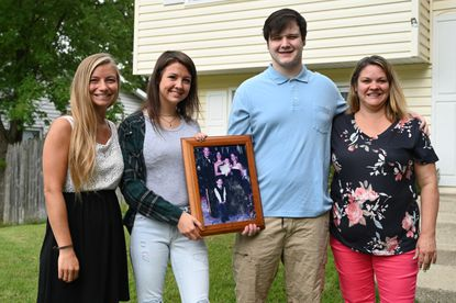 Amy Stoddard, right, and her children, from left, Megan, Makenzie and James III at their home in Crofton on Tuesday, Sept. 29. Pictured with them is the last family photo taken with Amy's husband Sgt. James Stoddard, before his death in Afghanistan 15 years ago.