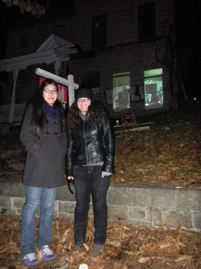 Filmmakers Sabrina Chin, left, and Melissa Crisco, with their film projecting on a house in the background.