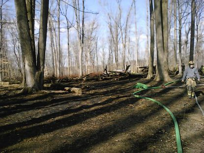 Firefighters work to contain a fire that burned several acres of woods in Fallston on Tuesday afternoon.