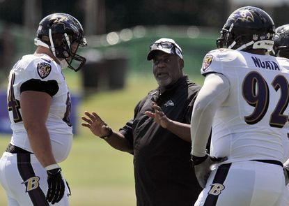 Ravens defensive line coach Clarence Brooks talks with Will Pericak (left) and Haloti Ngata during Monday's full-squad workout.