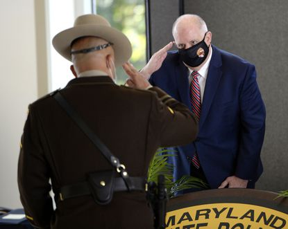Wearing a mask, Gov. Larry Hogan salutes Maryland State Police Trooper of the Year Kashef Khan in Sykesville on Wednesday.