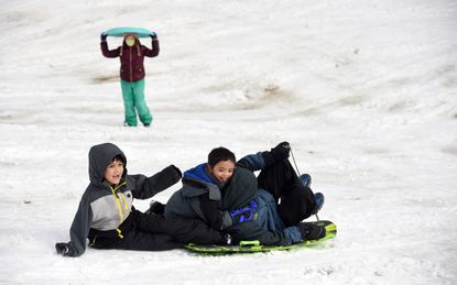 Josiah Sierra, left, and his friends Michael and Joshua McDonald enjoy a sled ride down a snowy hill by Longfellow Elementary in Columbia on Tuesday, Feb. 2, 2021.