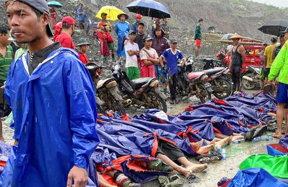 People gather near the bodies of victims of a landslide near a jade mining area in Hpakant, Kachine state, northern Myanmar, on July 2, 2020.