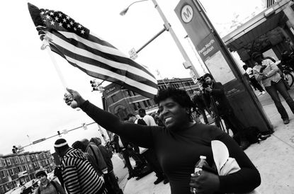 A reveler celebrates the decision to criminally charge all six police officers in the death of freddie gray.