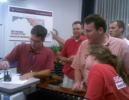 State Republican Party Chairman Alex Mooney, Del. Neil Parrott and others watch a state worker stamps documents showing they filed over 36,000 signatures opposing the new Congressional map.
