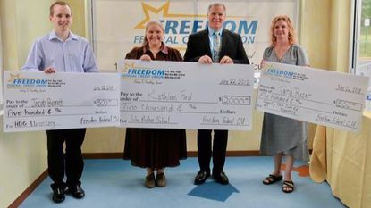 Freedom Federal Credit Union President and CEO Mike MacPherson, third from left, awards prize checks to 2018 Golden Apple Annual Education Award recipients, from left, Jacob Bennett, Kathleen Ford, and Tara Recor.