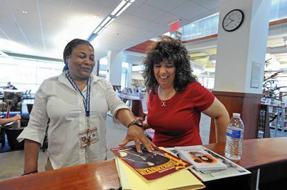 Michele Wojciechowski, right, of Kingsville, returns the graphic novel Mary Shelley's Frankenstein to the Enoch Pratt Library's Southeast Anchor library in Highlandtown 34 years after it was due.