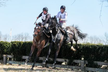 Teammates Eddie Keating, left, and Amber Hodyka, clear the hedge jump, which signals the half point of the race.
