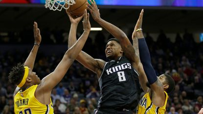 Sacramento Kings forward Rudy Gay, center, goes to the basket between Indiana Pacers Myles Turner, left, and Paul George during the second half of an NBA basketball game Wednesday, Jan. 18, 2017, in Sacramento, Calif. The Pacers won 106-100.